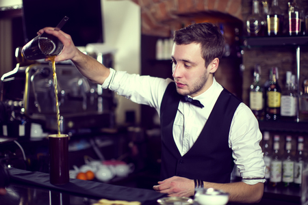 bartender: young man working as a bartender in a nightclub bar Stock Photo