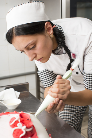 whipped cream: pastry chef decorates a cake in a candy store Stock Photo