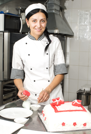 candy store: pastry chef decorates a cake in a candy store Stock Photo
