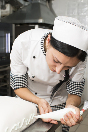 decorates: pastry chef decorates a cake in a candy store Stock Photo
