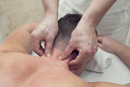 collo: un uomo in un salone di massaggi facendo massaggio alla testa