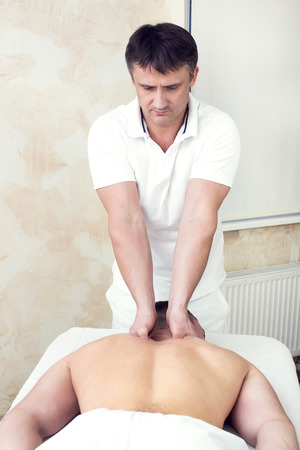 physiotherapy: man doing sports massage at the massage parlor