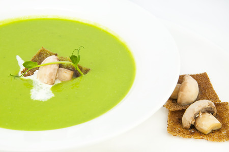 recipe decorated: pea soup on a white dish at restaurant