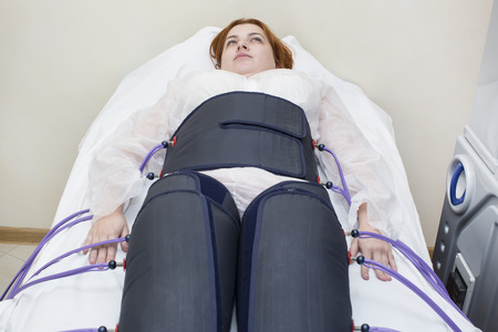 orthopedist: woman at the clinic for the treatment of pressure therapy procedure