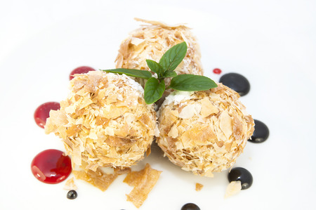 splurge: balls of ice cream decorated with mint on a white background in the restaurant