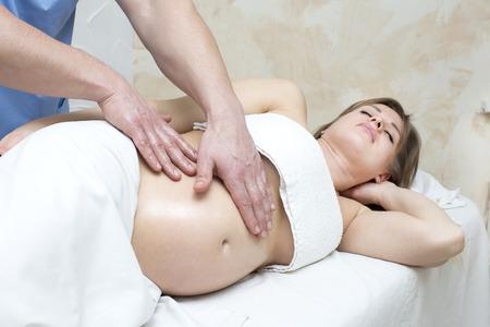 masaje: salón de procesos que hace el masaje a una mujer embarazada Foto de archivo