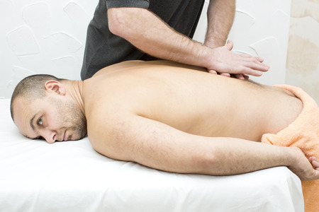sports massage: hombre haciendo masaje deportivo en la sala de masajes
