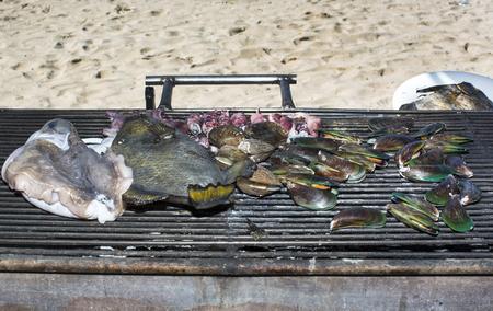 molluscs: grilling seafood assortment of fish, shells of molluscs