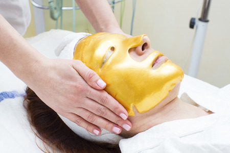 gold facial: gold mask cosmetic procedure in the beauty salon Stock Photo