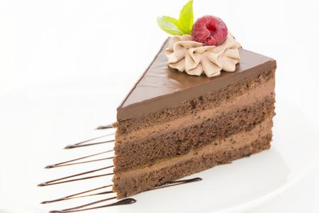 porcion de torta: Praga pedazo de pastel decorado con frambuesas sobre un fondo blanco