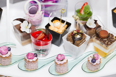 canapes in plastic cups decorated with edible flowers