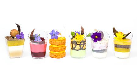 los mini canapés en vasos de plástico decorado con flores comestibles Foto de archivo
