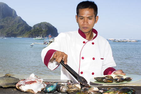 nido: Filipino chef preparing a meal on the grill on the coast of El Nido Stock Photo