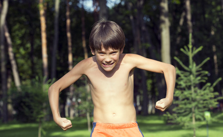 individuals: portrait of a boy in nature which shows his muscles