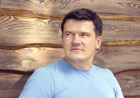 only the biceps: portrait of a man against the backdrop of wooden planks Stock Photo
