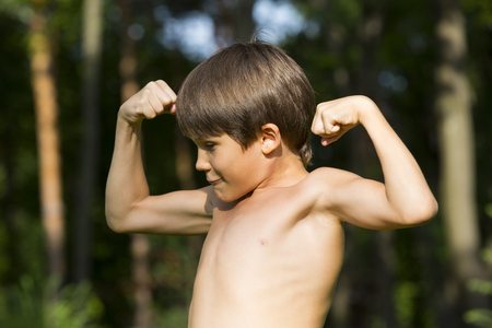 only the biceps: portrait of a boy in nature which shows his muscles