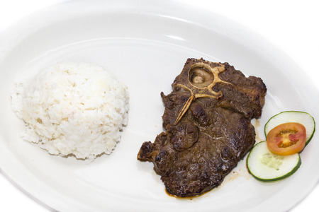 t bone: T Bone steak with rice and sauce on a white plate in a restaurant