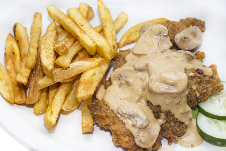 Schnitzel with mushroom sauce and french fries on a white background in the restaurant Stock Photo