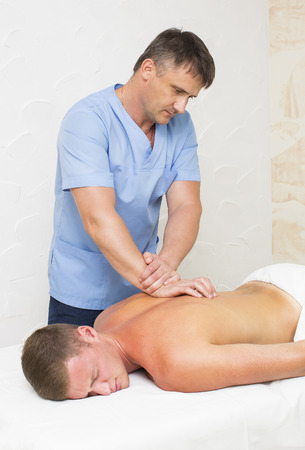 masaje deportivo: young man on wellness treatments sports massage Foto de archivo