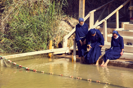 nuns: BETHABARA, ISRAEL - OCTOBER- 7, 2016: Pilgrims Catholic nuns on the banks of the Jordan River at the site of Jesus baptism. Israel - 2016