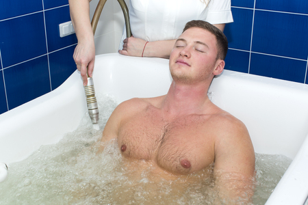 The young man is the procedure in the whirlpool hydrobath Stock Photo