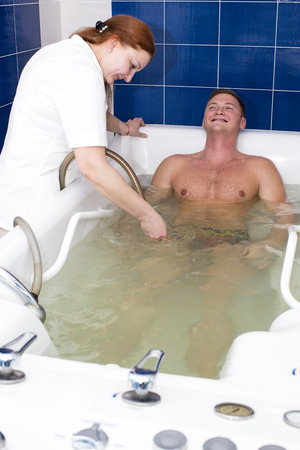 hydromassage: The young man is the procedure in the whirlpool hydrobath Stock Photo