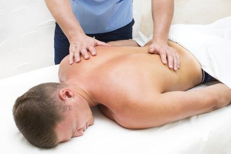 masaje deportivo: young man on wellness treatments sports massage Foto de archivo
