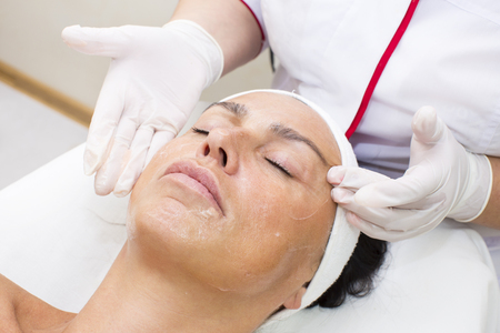 woman's hands: process of massage and facials in beauty salon