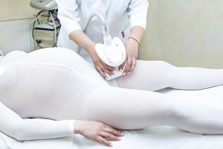 pregnant woman takes medical procedure at the clinic lipomassage