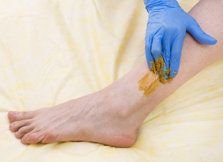 depilate: Epilation sugar processes woman passes in a beauty salon
