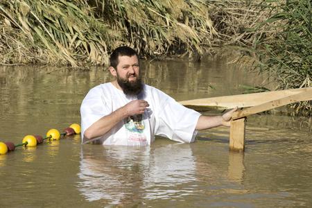 BETHABARA, JORDAN - JANUARY - 11, 2017: Man middle-aged pilgrim passes in the River Jordan Baptism in the Jordan. JORDAN - 2017 Editorial