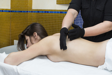 The process of massage in massage glove woman in a beauty salon