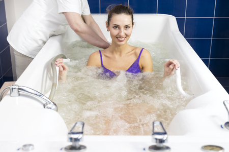 Young woman during hydromassage in beauty salon Фото со стока