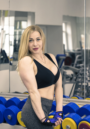 muscle gain: A young girl is engaged in power fitness in the gym