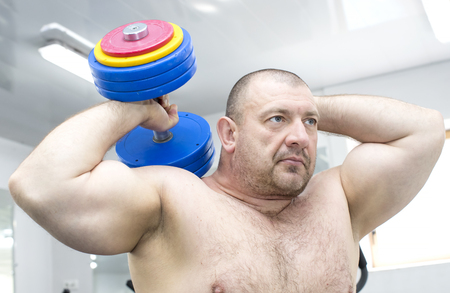 The adult brutal man is engaged in power bodybuilding in the gym Stock Photo