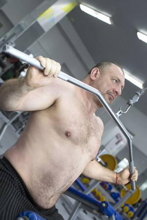 brutal: The adult brutal man is engaged in power bodybuilding in the gym Stock Photo