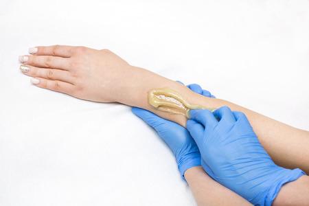 Epilation sugar processes woman passes in a beauty salon
