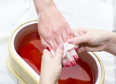 Proces paraffine behandeling van vrouwelijke handen in schoonheidssalon Stockfoto