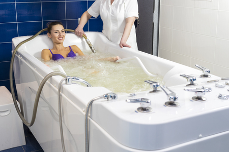 Young woman during hydromassage in beauty salon Stock Photo
