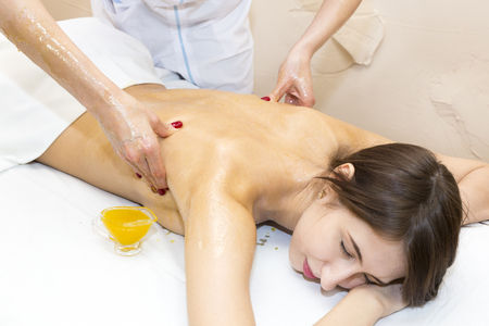 pamper: Girl treatment massage honey body wrap in a beauty salon