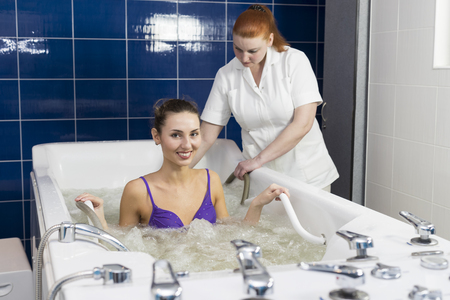 woman in bath: Young woman during hydromassage in beauty salon Stock Photo