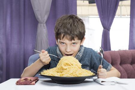 The boy is appetizing eats a large Italian spaghetti