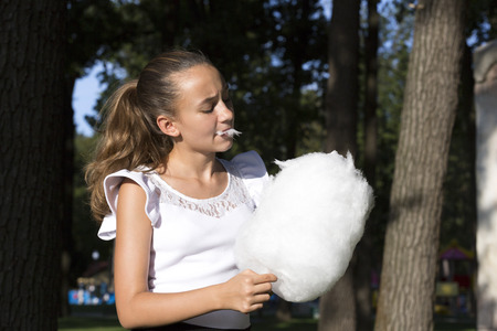 children party: Girl eating cotton candy in a summer park