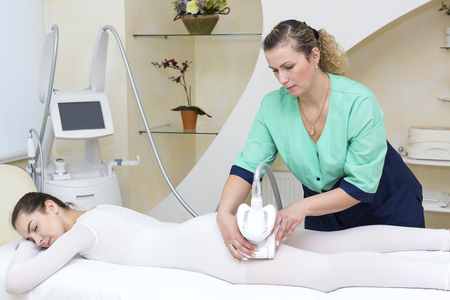 The procedure of lipomassage in a beauty salon makes a woman Stock Photo