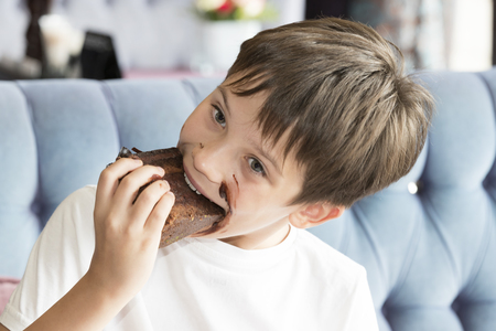 The boy is eating a large piece of cake in his hands