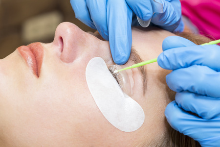Woman on the procedure for eyelash extensions, eyelashes lamination