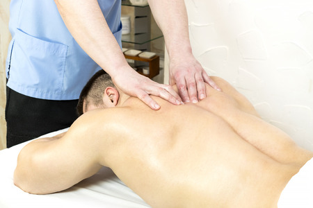 The process of sports massage is made by a man in a massage salon