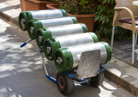 storage: A cart loaded with kegs and beer on a city street