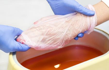Proces paraffine behandeling van vrouwelijke handen in schoonheidssalon