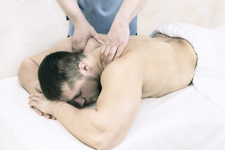 The process of health-improving sports massage is made by a man in a medical clinic